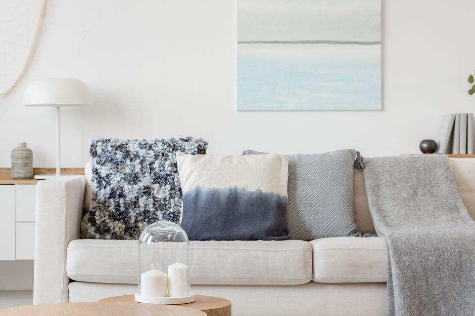 Abstract paste blue and white painting on empty white wall behind beige couch with pillows