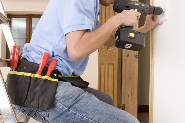 Electrician drilling an outlet in a wall