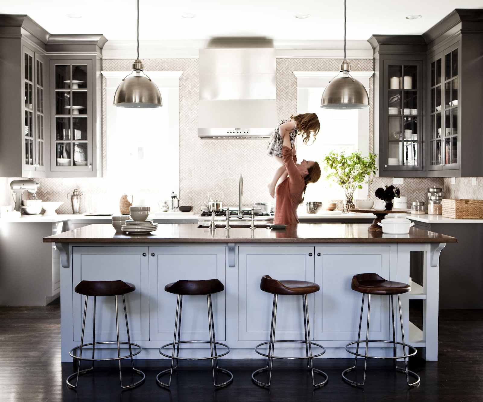 Woman lifting up her daughter in a kitchen with an island, four bar stools, and hanging pendant lights.
