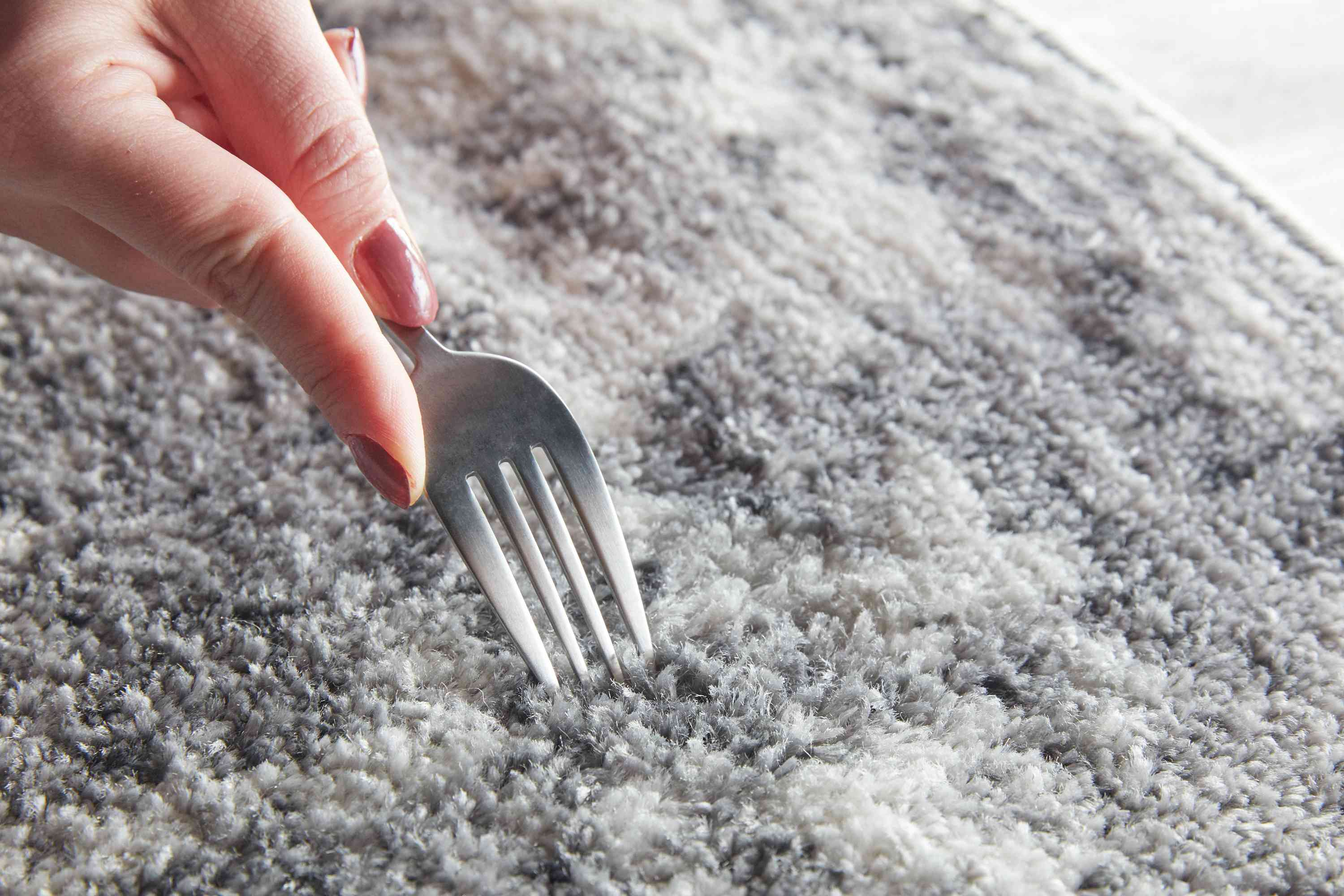 using a fork to fluff up the rug fibers