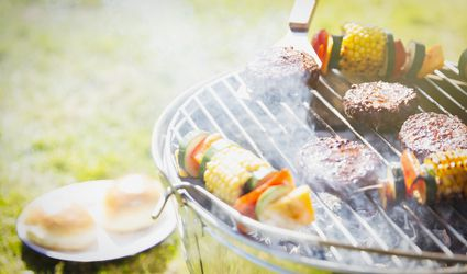 Hamburgers and vegetable skewers on barbecue grill