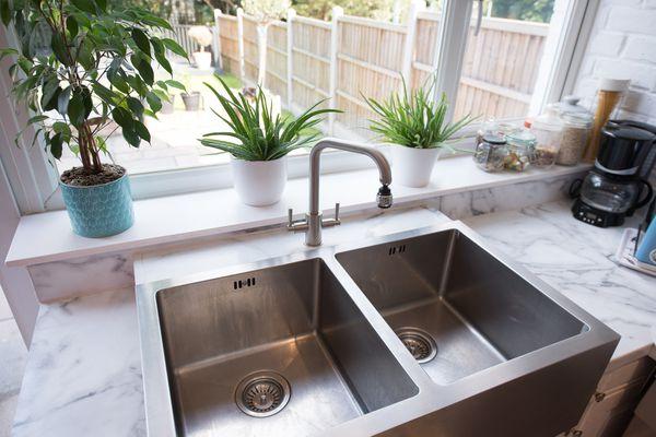 A double sink in a kitchen window