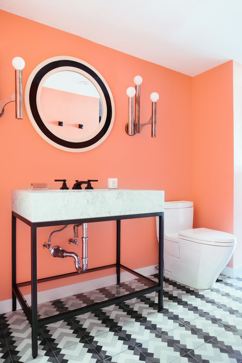 Bathroom with coral walls and black accents