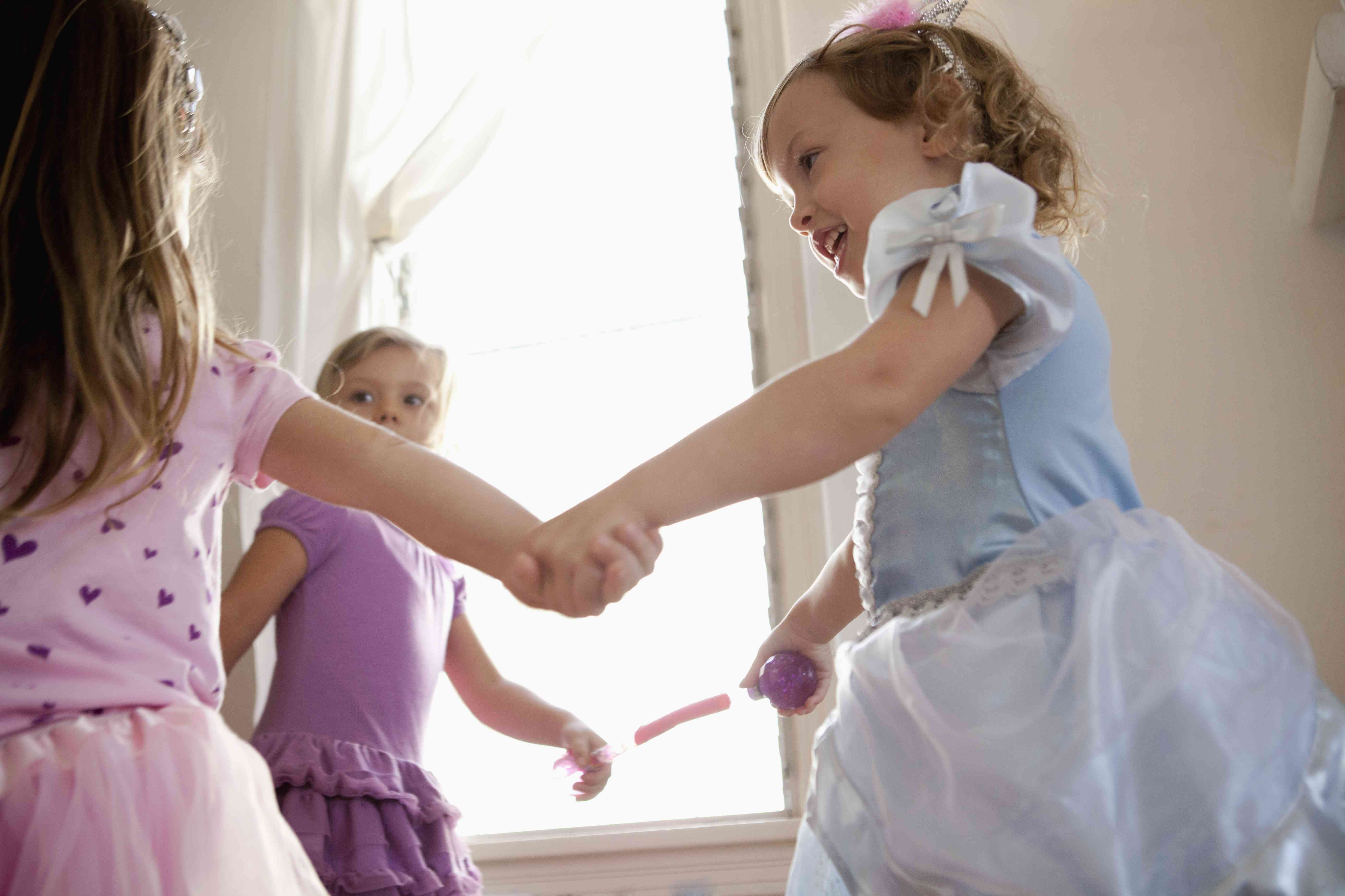 Three young girls in party dress holding hands and dancing