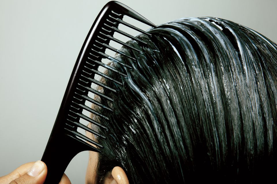 woman combing leave-in conditioner through hair