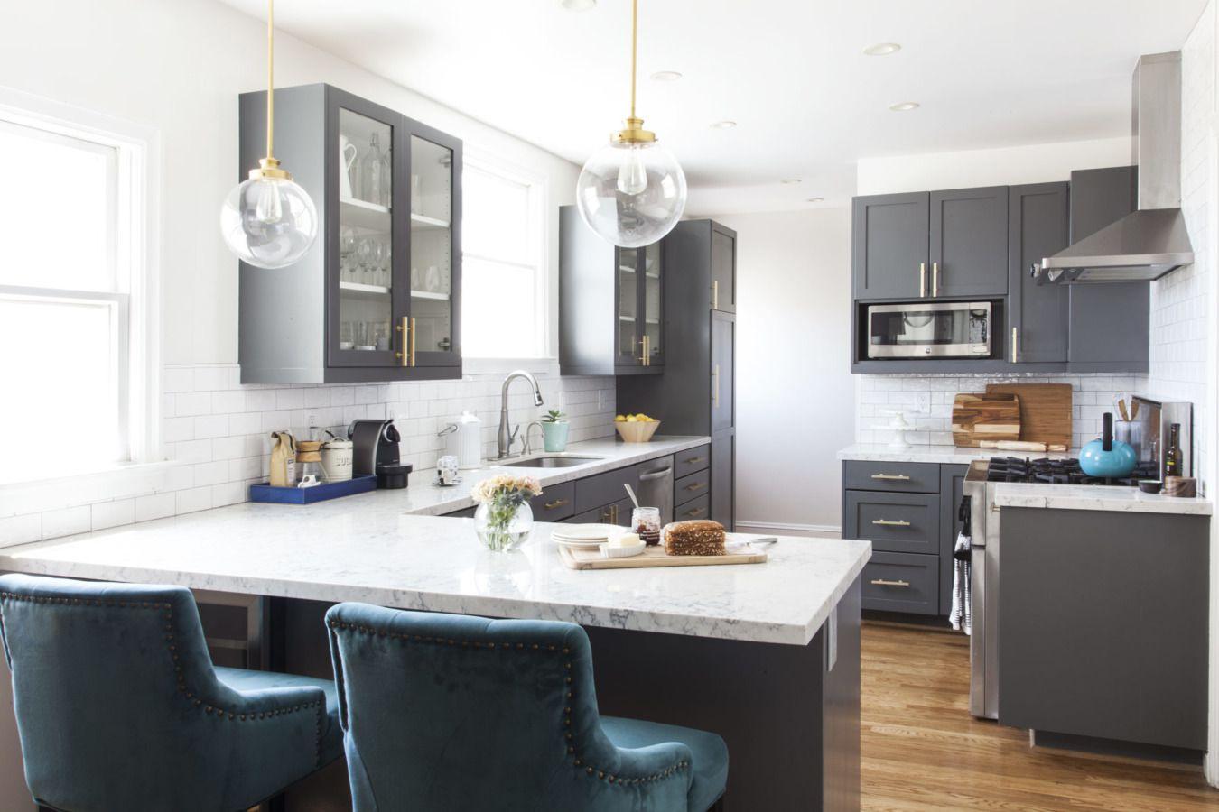 Cocina de mármol y cuarzo con sillas azules y blancas