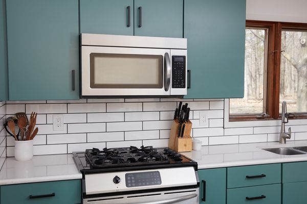 Stainless steel stove and microwave surrounded by green kitchen cabinets