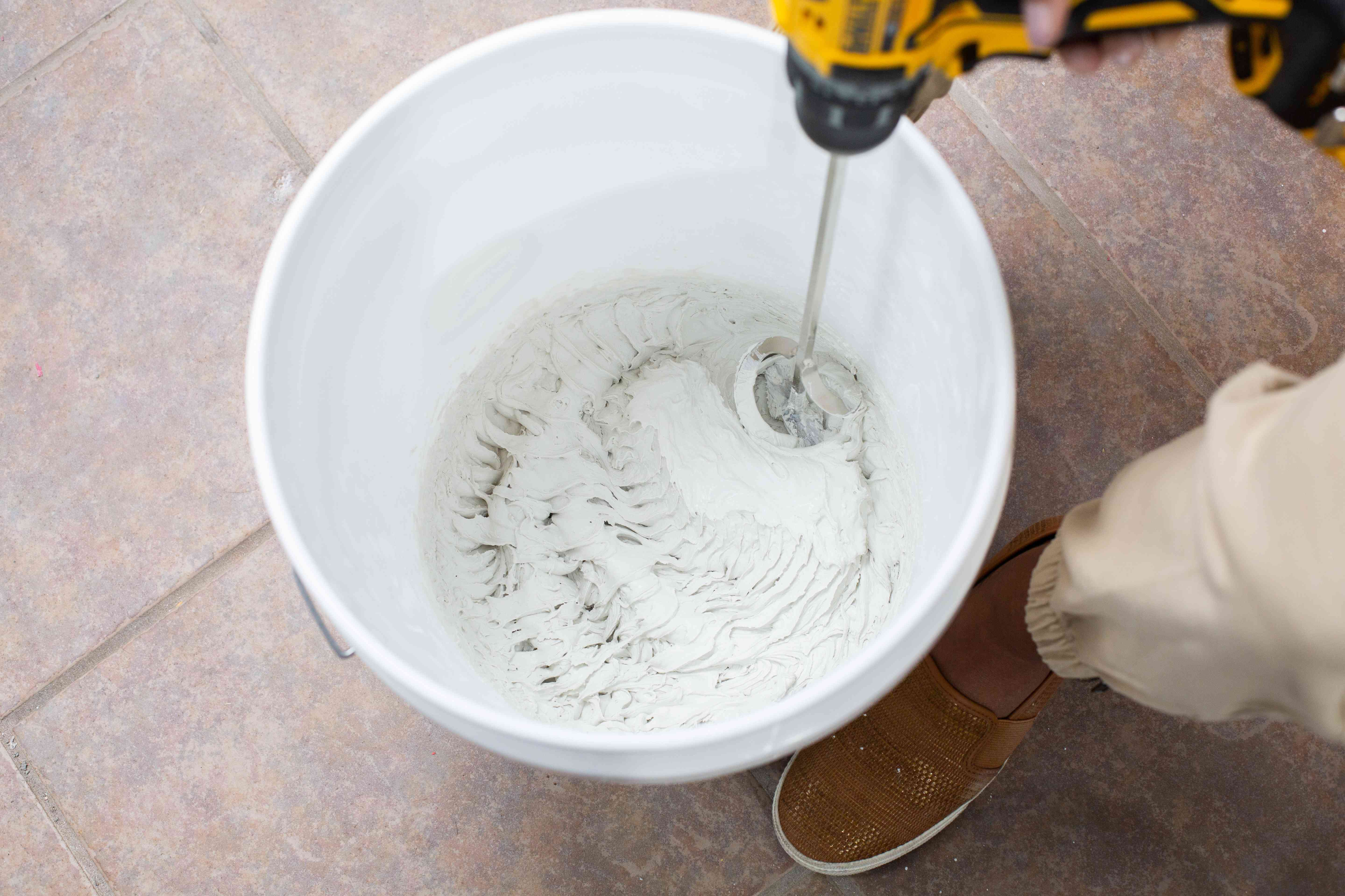 Plastic bucket with plaster adhesive being churned with yellow electric drill