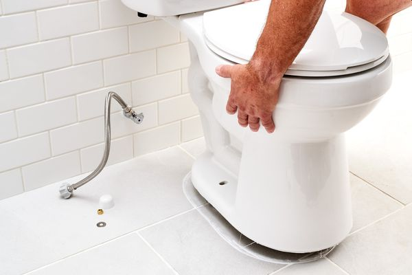 Bathroom toilet being removed from floor with shutoff valve disconnected