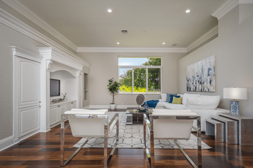 A living area that is light and bright with white sofa and chairs and a big window without window treatments