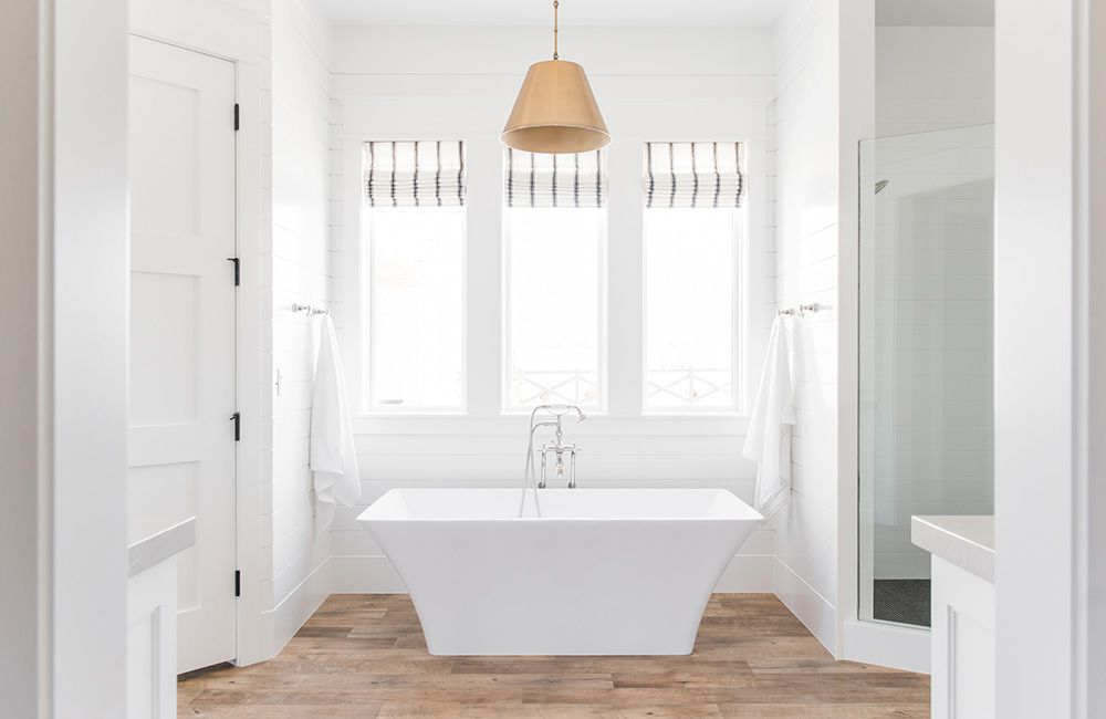 Lámpara colgante dorada sobre baño blanco nítido