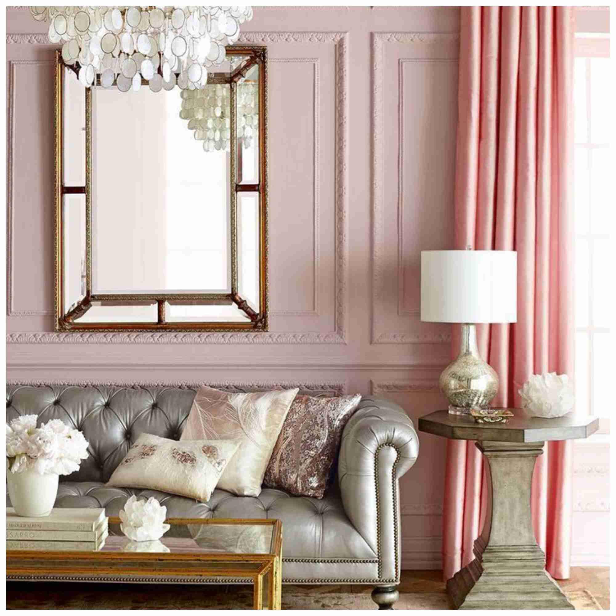 Sala de estar, paredes rosadas, con sofá plateado y espejo grande .