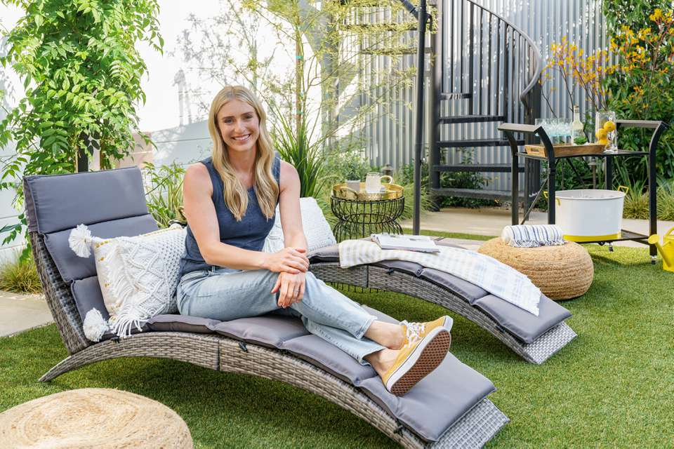 HGTV star Jasmine Roth poses on a foldable faux rattan lounge chair in her backyard