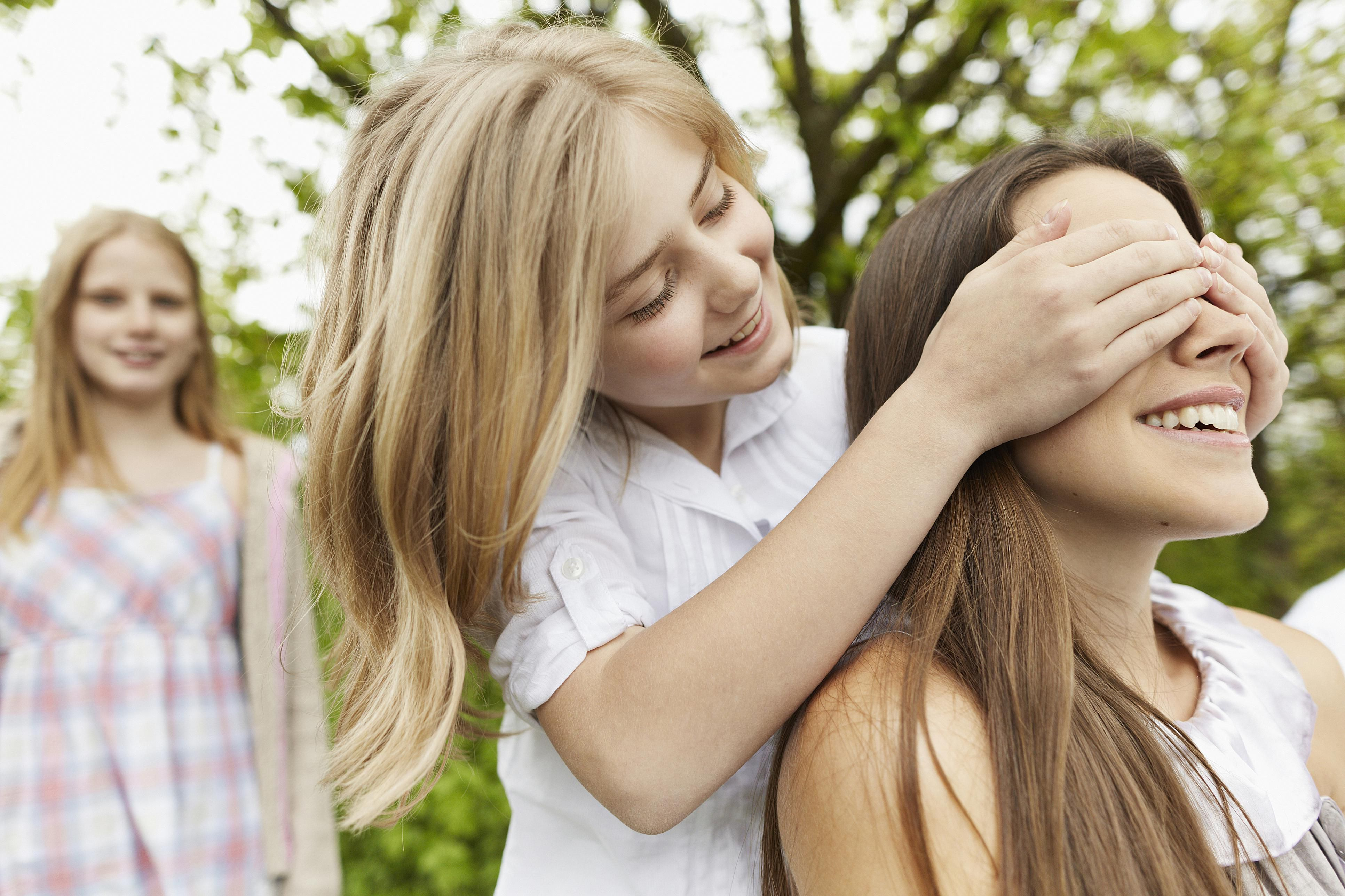 Girl covering woman's eyes outdoors