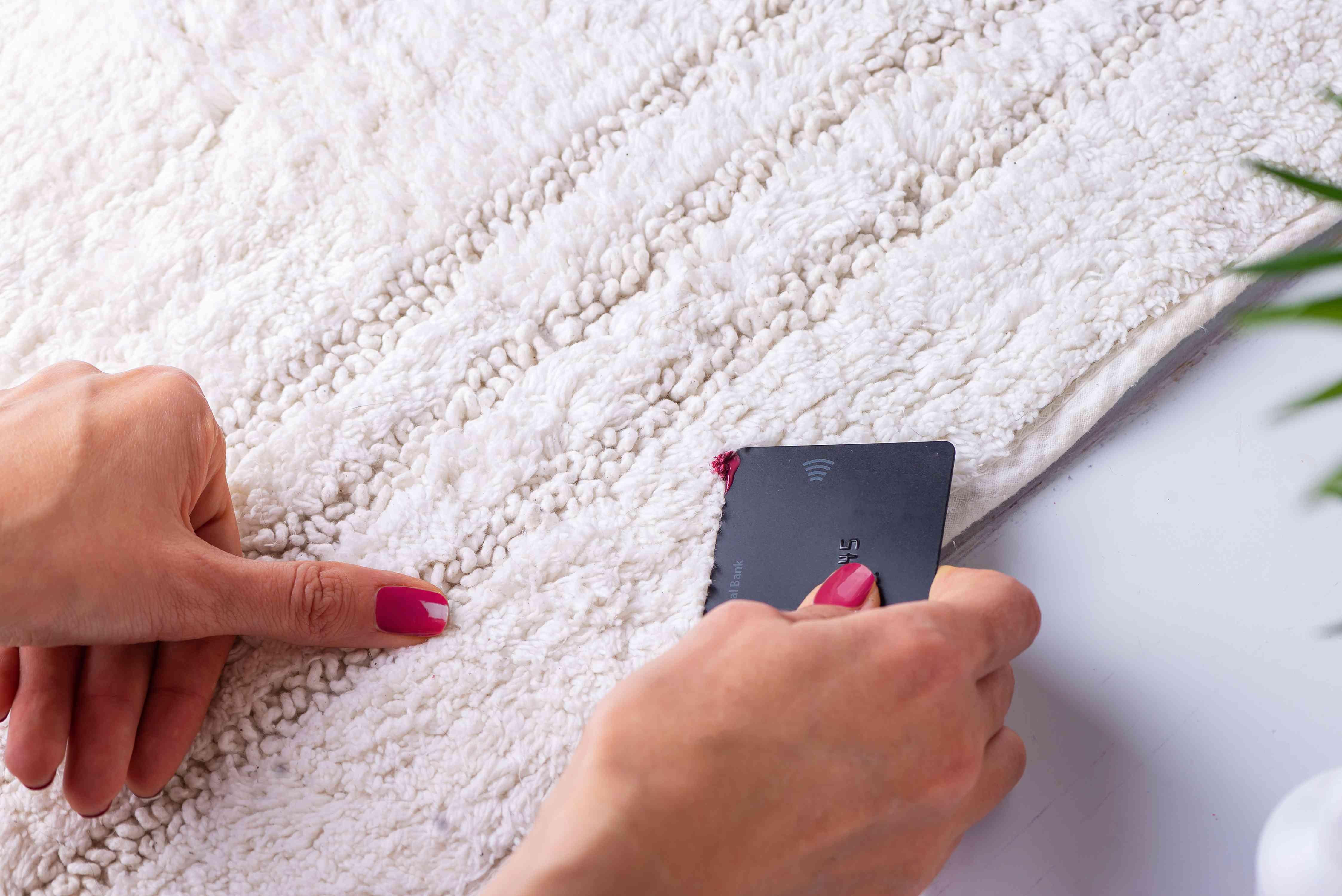 using a credit card to scrape away extra nail polish