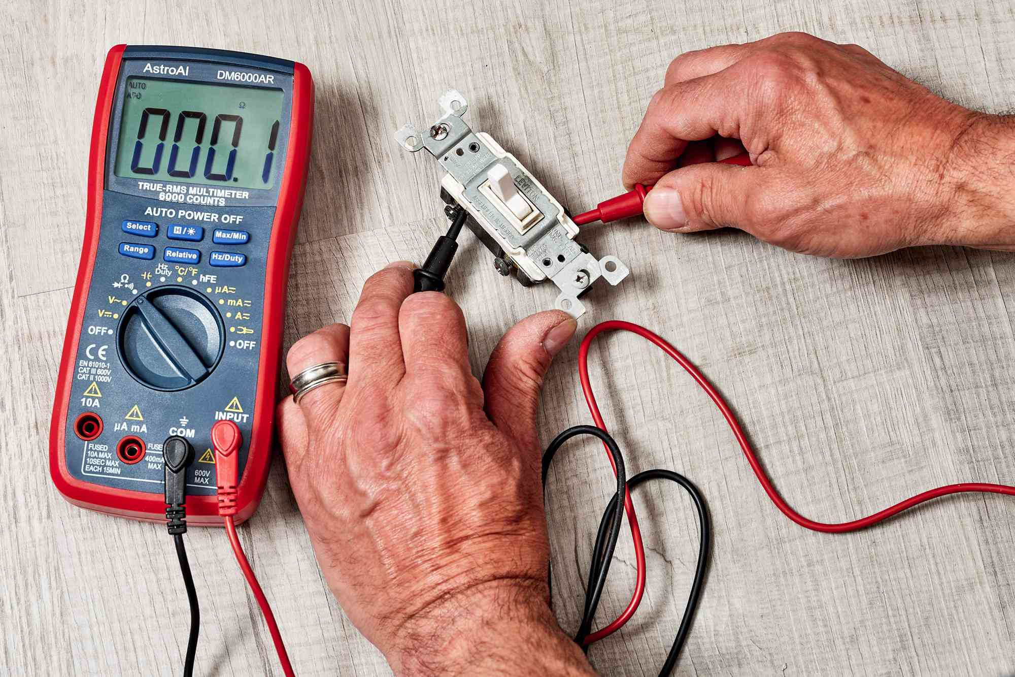 Wires clipped to continuity tester and common screw terminal touching the tester probe
