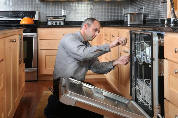 a repairman working on a dishwasher in a home kitchen