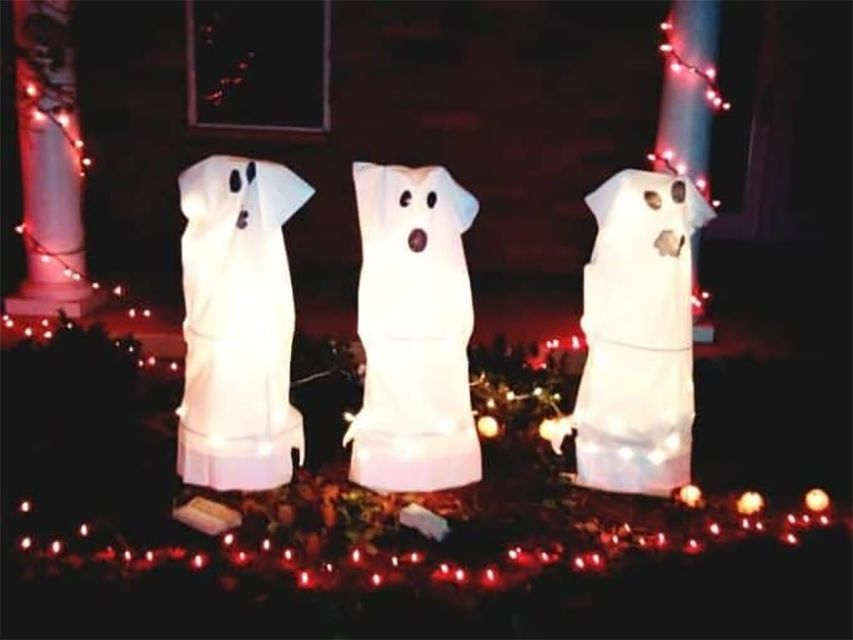 Three ghosts lit up in a yard