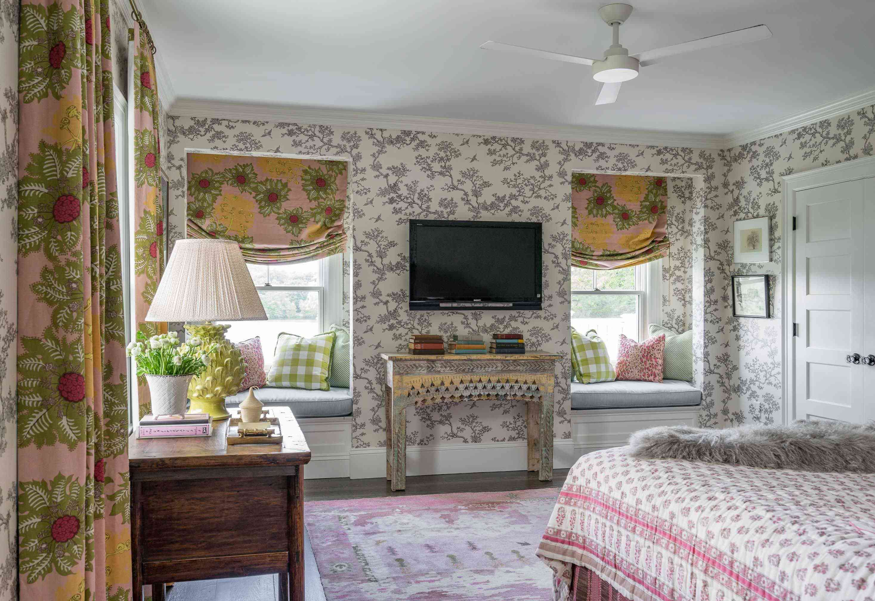 floral wallpaper adorns the walls of this cottagecore bedroom with floral window treatments, fresh flowers, and a floral quilt