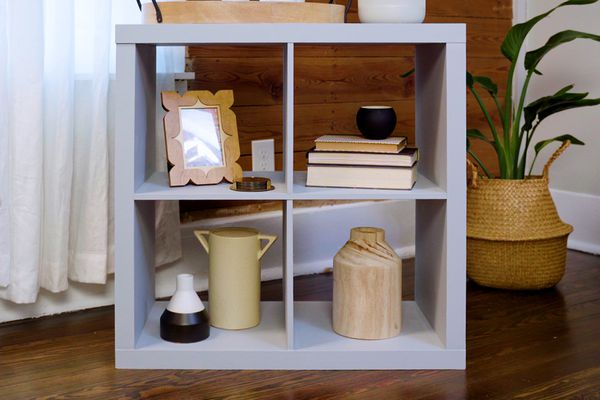 Refurbished particleboard furniture with gray paint and decor items displayed in square shelves
