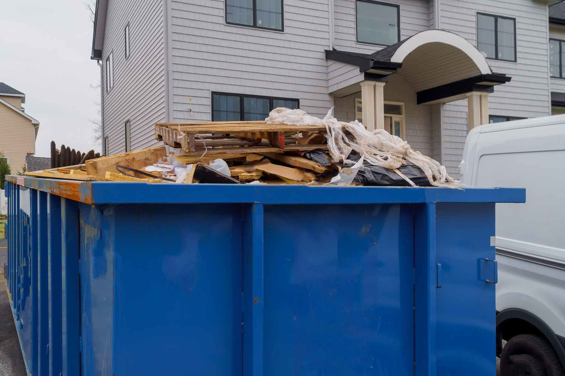 a blue dumpster filled with trash outside a home