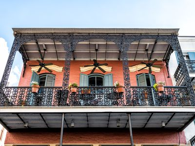 New Orleans, USA French quarter with wrought cast iron balcony of building in traditional architecture with potted plants decoration in Louisiana famous city