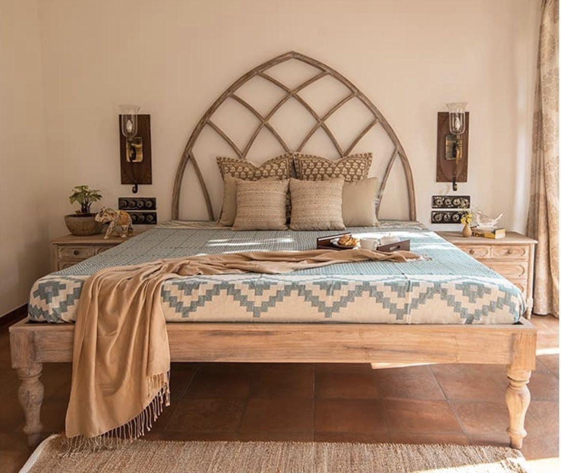 mediterranean bedroom with terra cotta tile floors, wooden scones, blue pattern bedspread