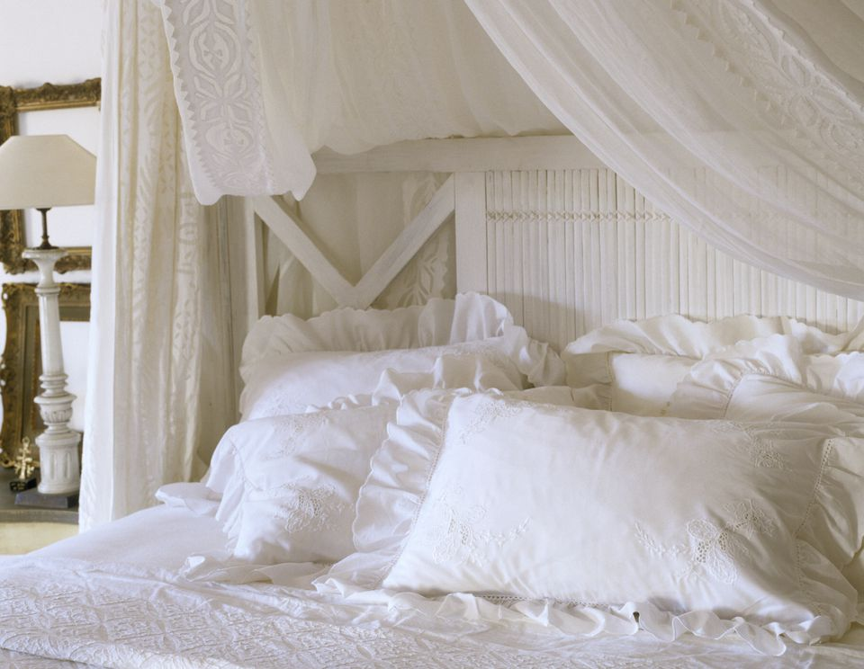 White bedroom with pillows, headboard, and draped linen.