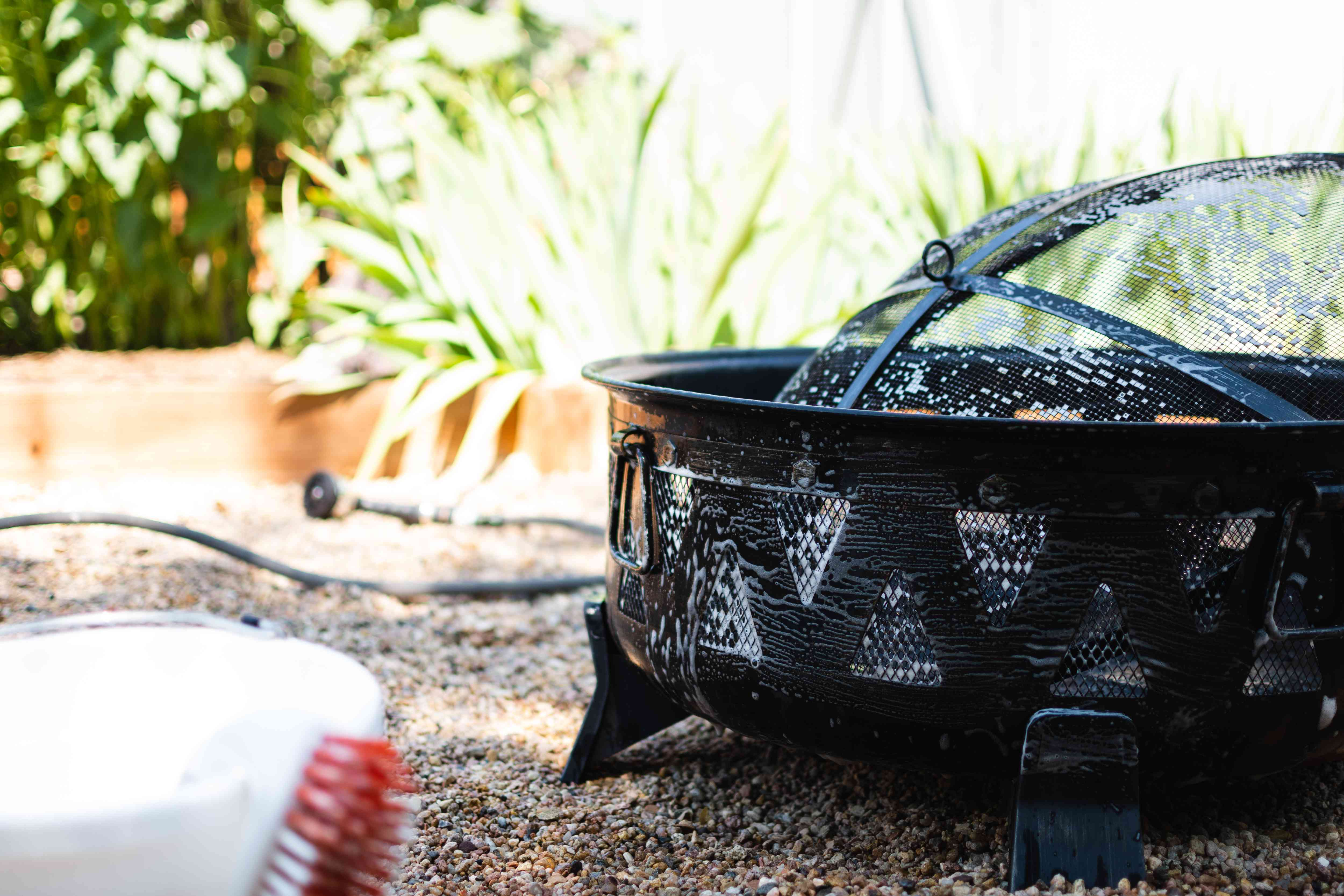 Black metal fire pit scrubbed with cleaning solution