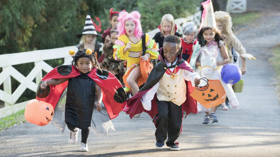Children wearing costumes on Halloween running in park