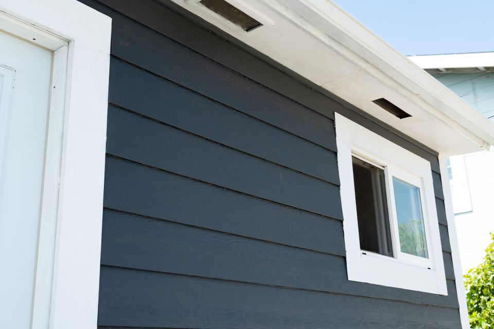 Dark blue fiber-cement siding on side of house trimmed with white paint