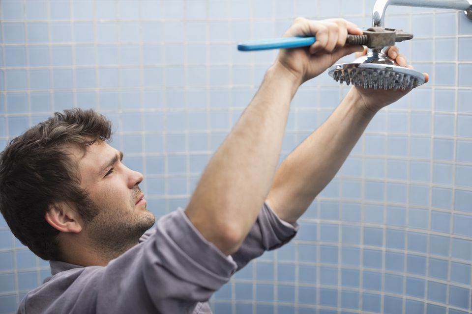 Plumber working on shower head in bathroom