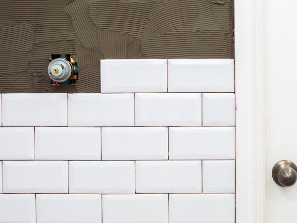 White ceramic wall tile installed on half of a wall and other half exposed with adhesive