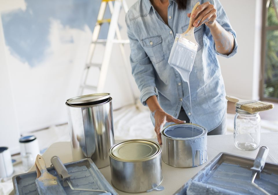 Woman dipping a paintbrush into a can of blue paint