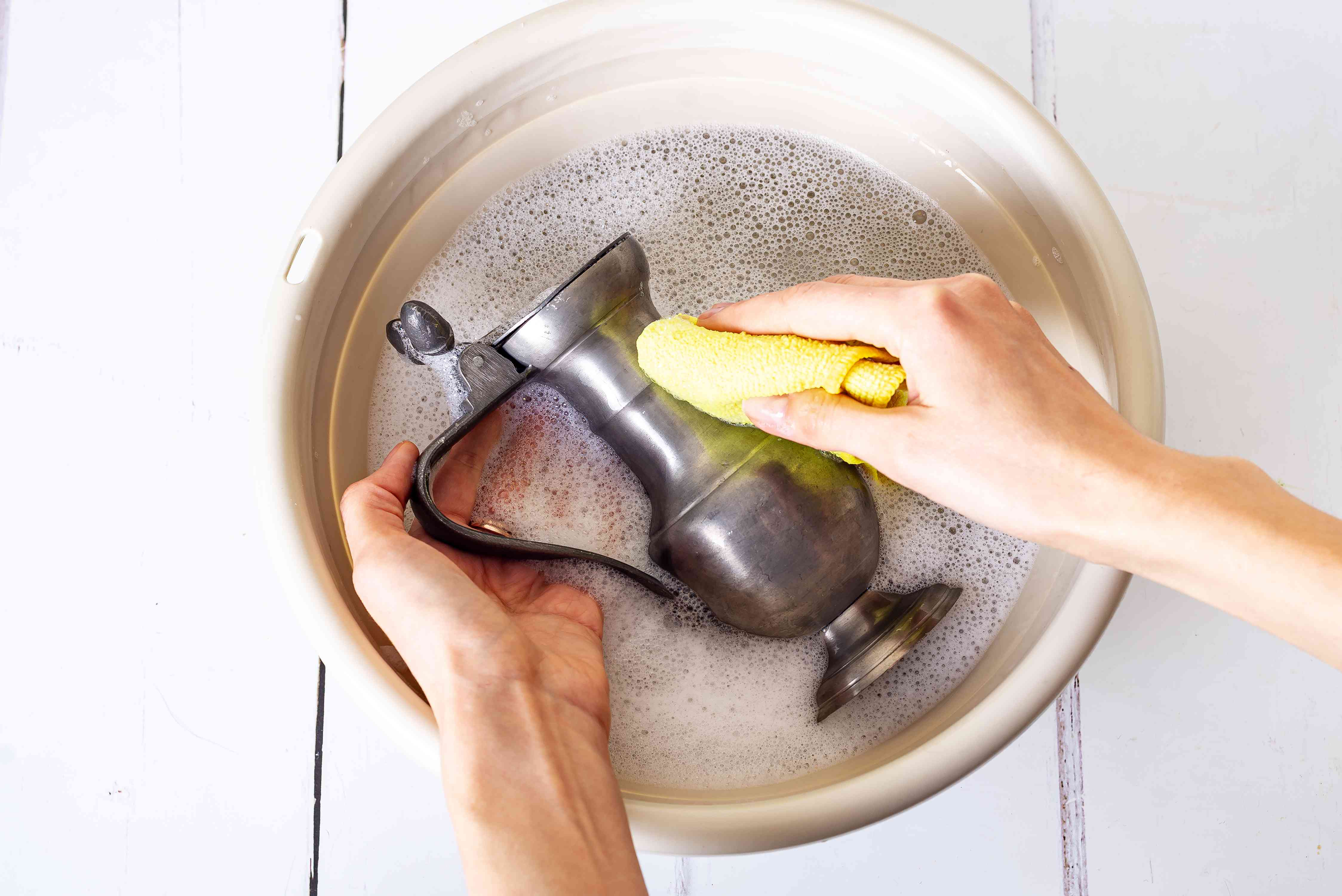 Pewter dispenser washed with yellow cloth in bucket filled with cleaning solution