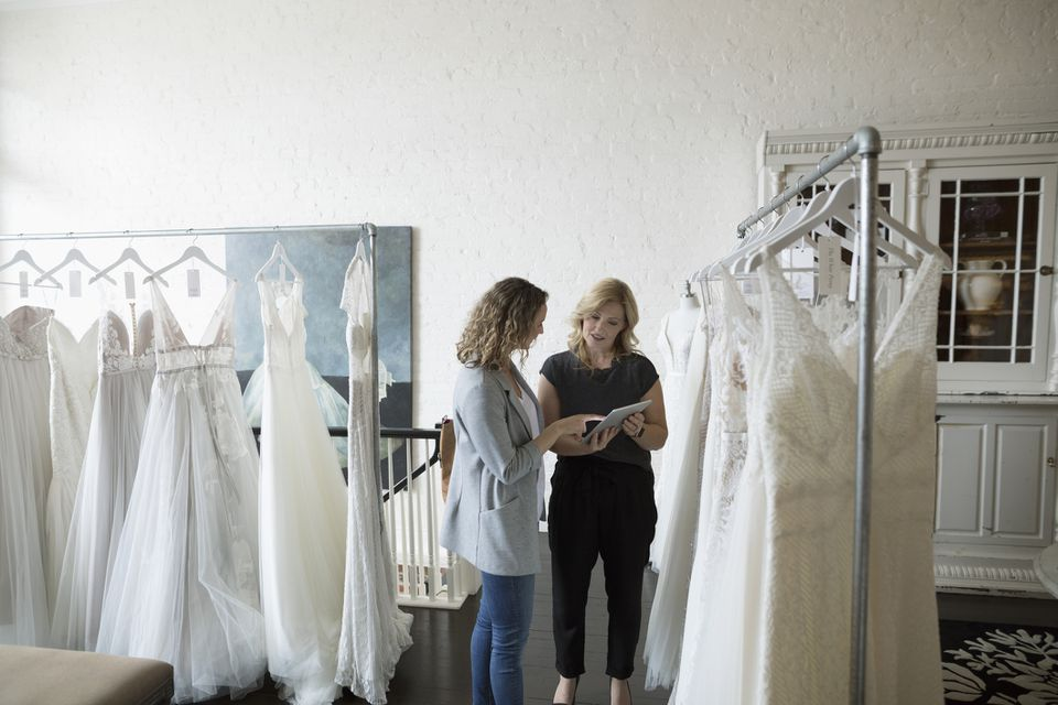 Bridal shop owner helping bride with digital tablet shop for wedding dress