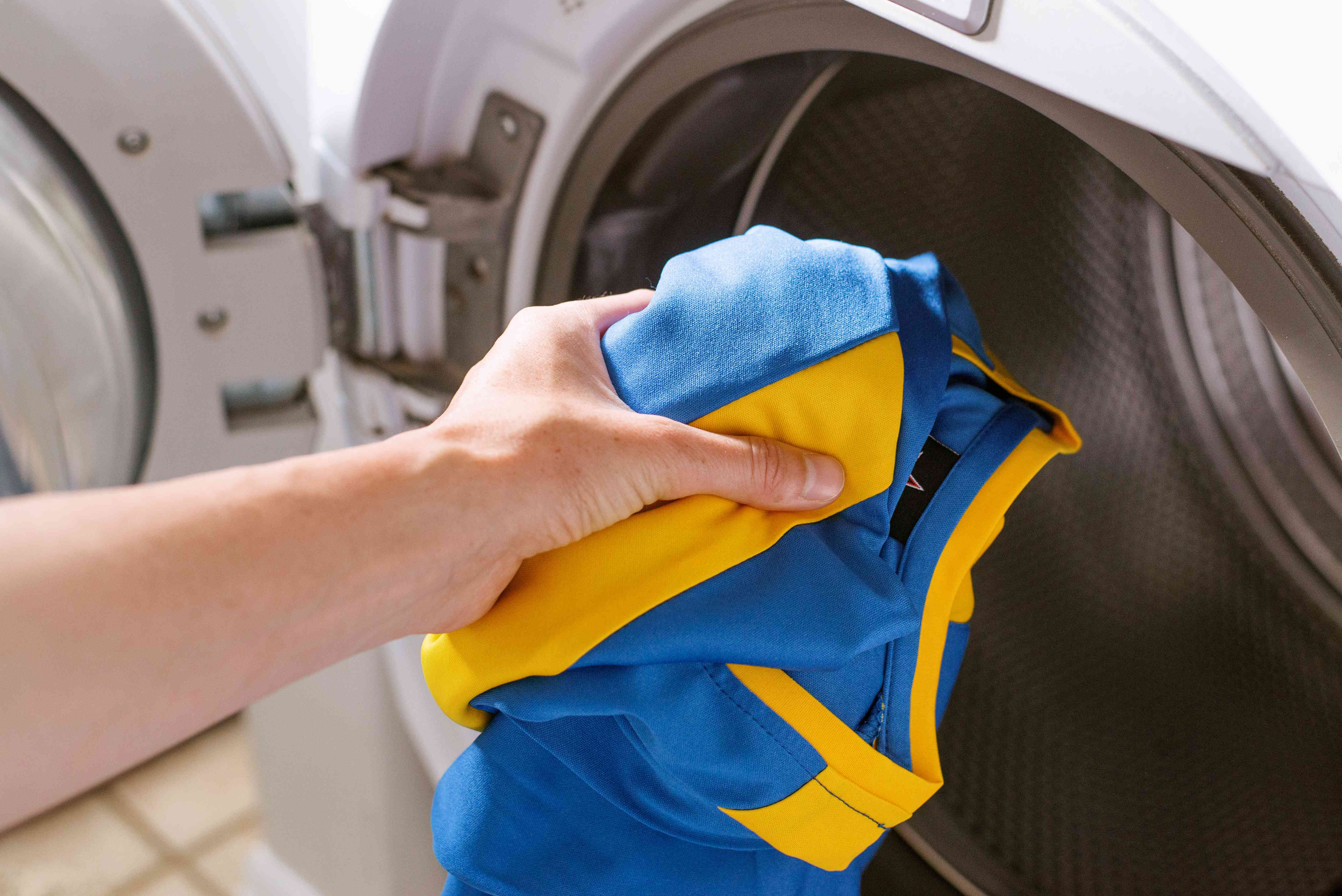 Blue and yellow soccer uniform placed in washing machine alone