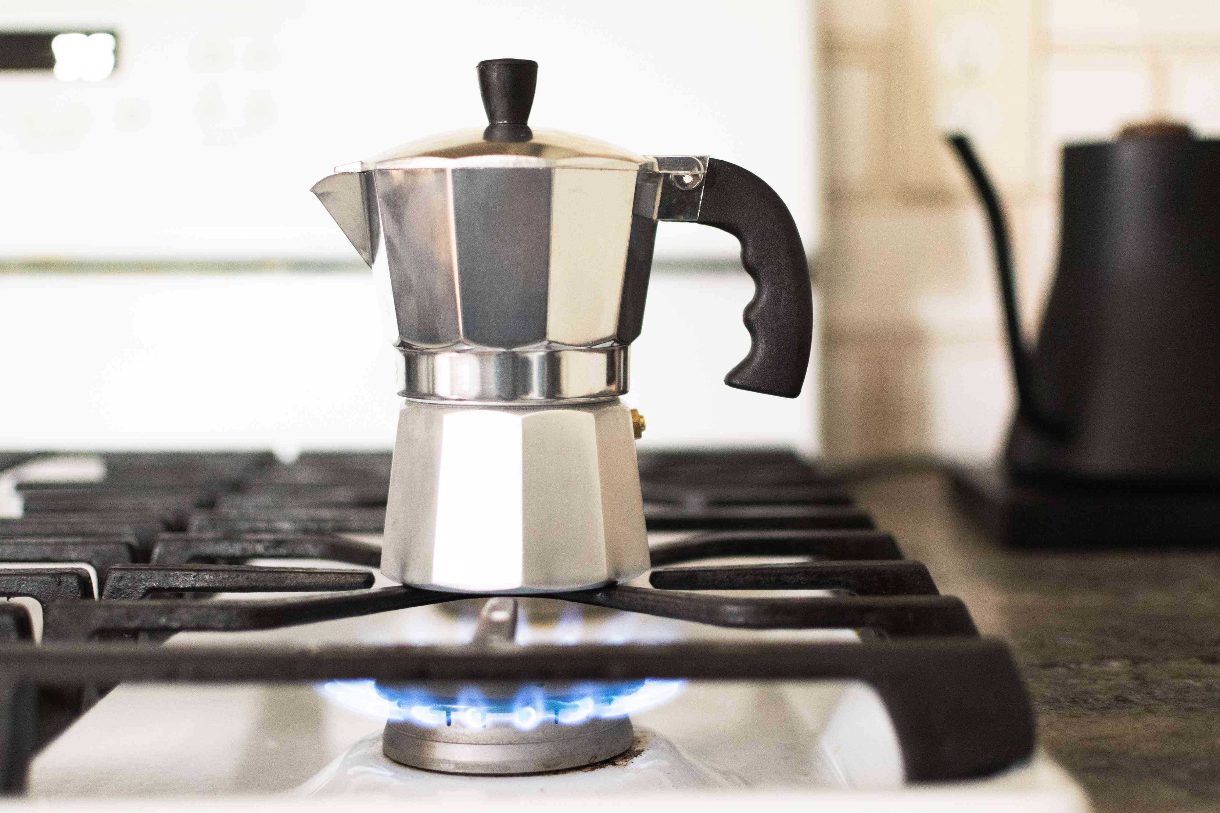 Stovetop lighted with Moka pot brewing water and distilled vinegar solution