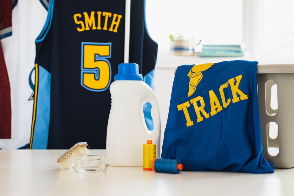 Team jerseys air drying next to cleaning materials and laundry basket