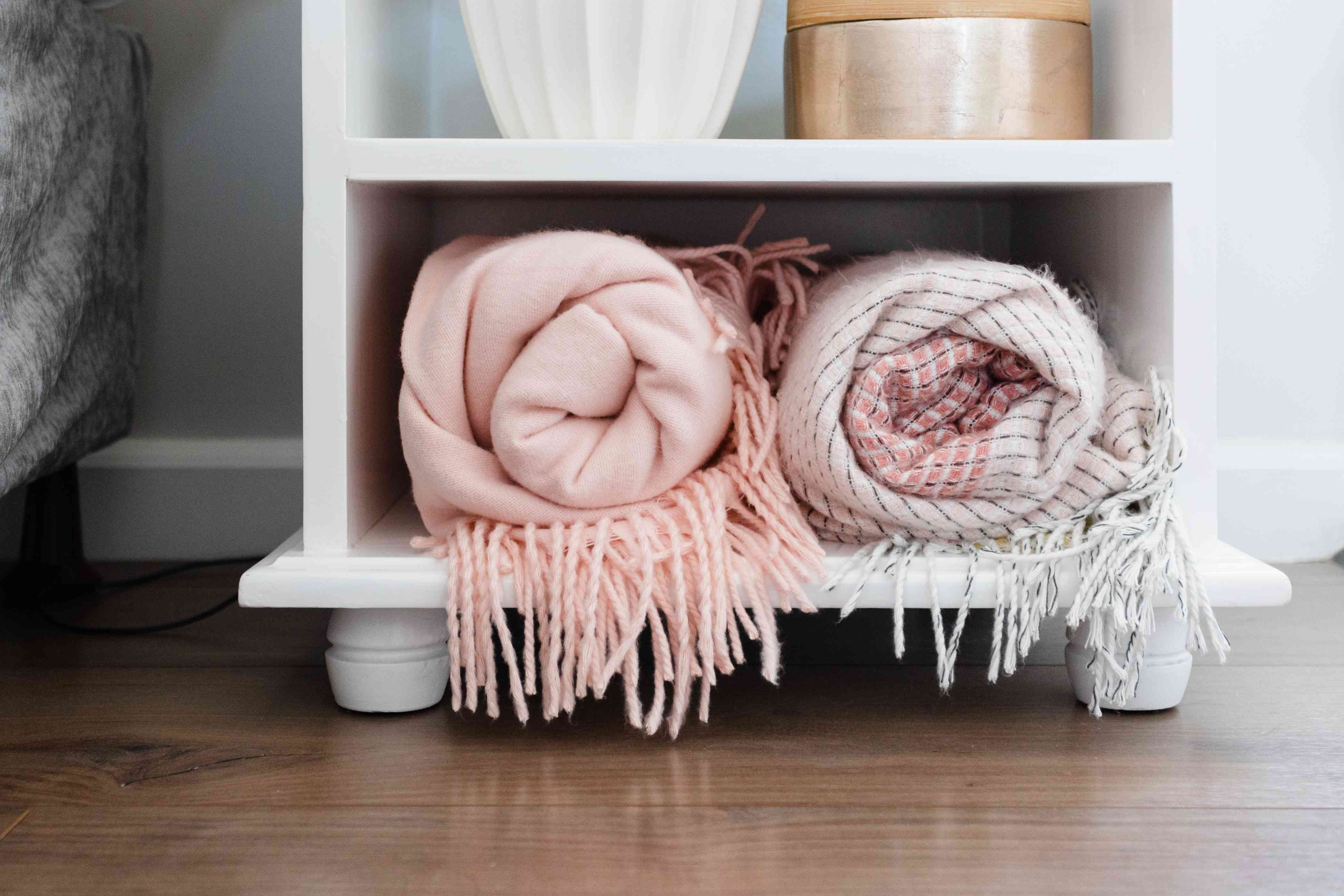 Throw blankets rolled into bottom shelf of white nightstand