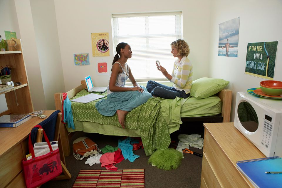 Two young women sitting on bed in student dormitory, facing each other