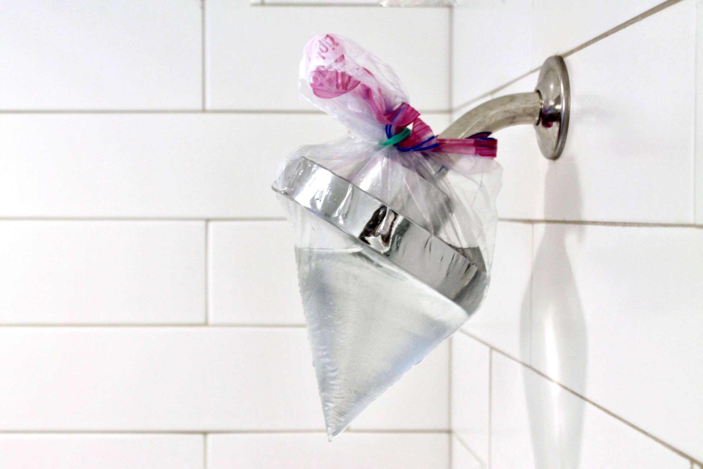 plastic bag filled with vinegar tied around a shower head