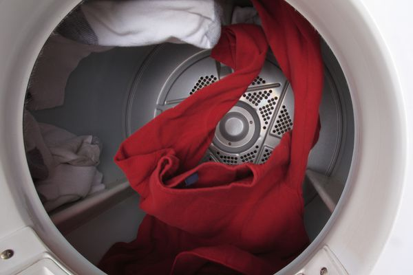 Clothes tumbling in an open dryer.