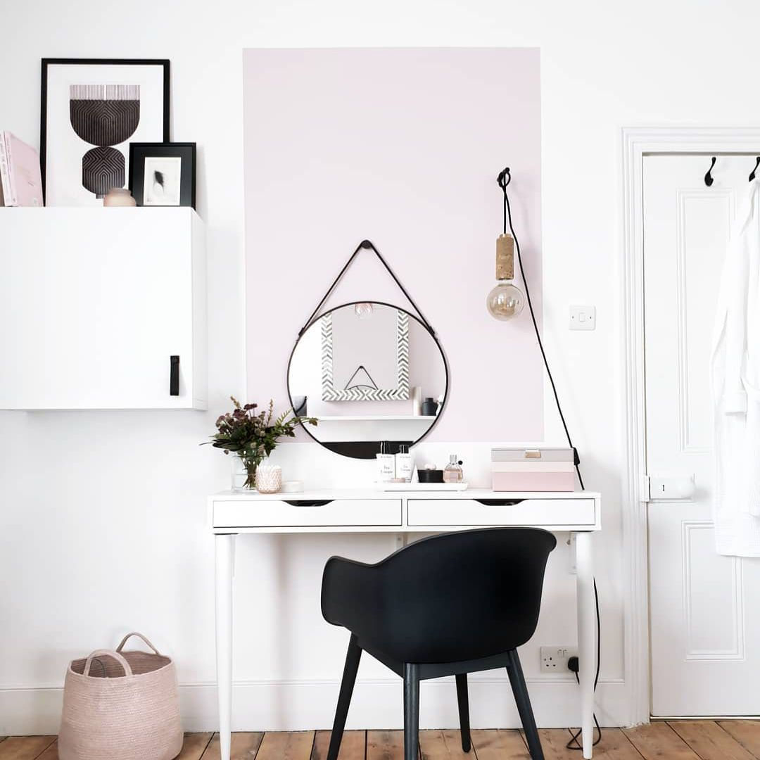 white desk with a pink basket on the floor next to it
