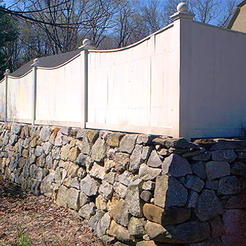 Picture of a wooden fence perched on a stone wall.