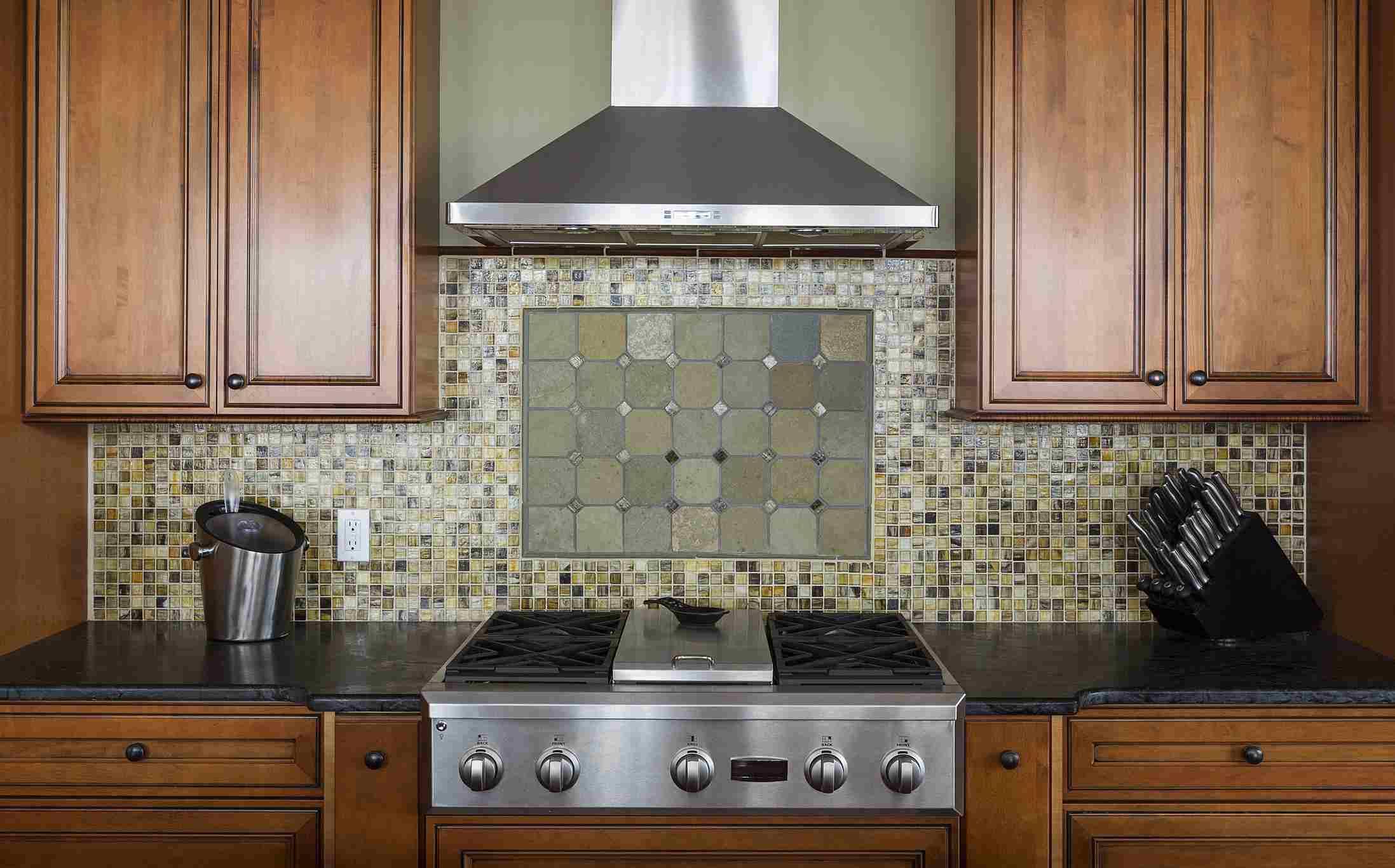 Tile back splash, ventilation hood and stove in kitchen