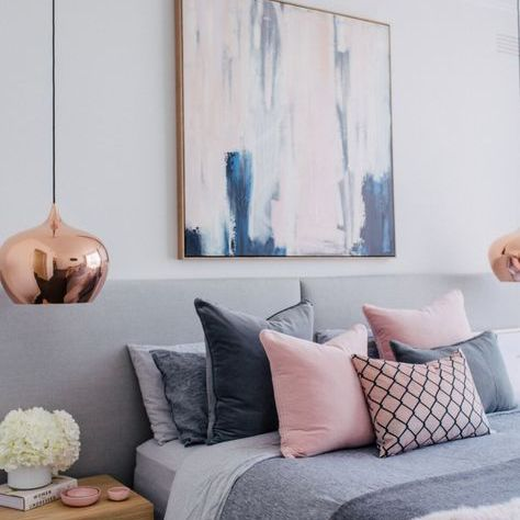 A bedroom with blush and gray colors