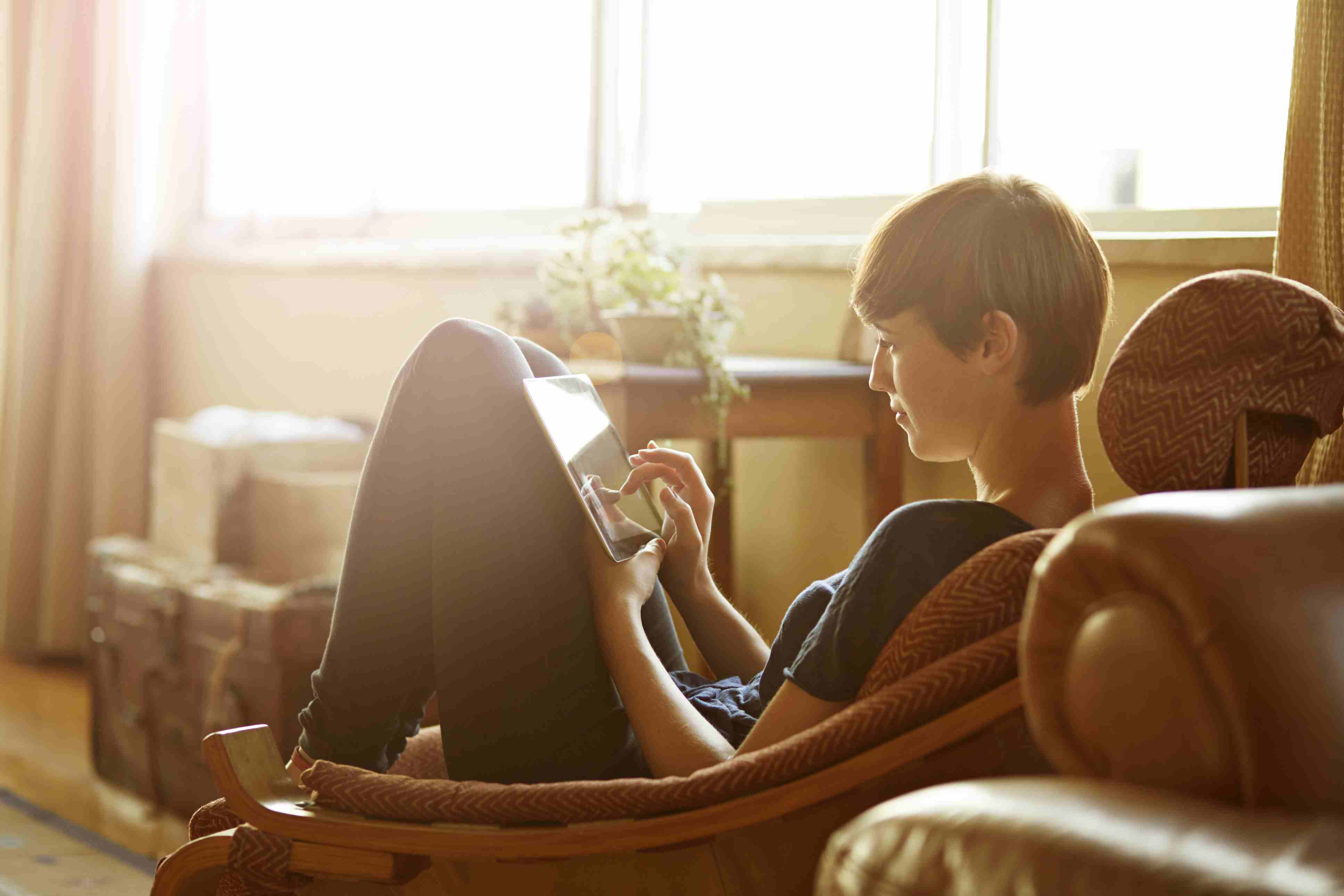 Young woman relaxing at home with tablet