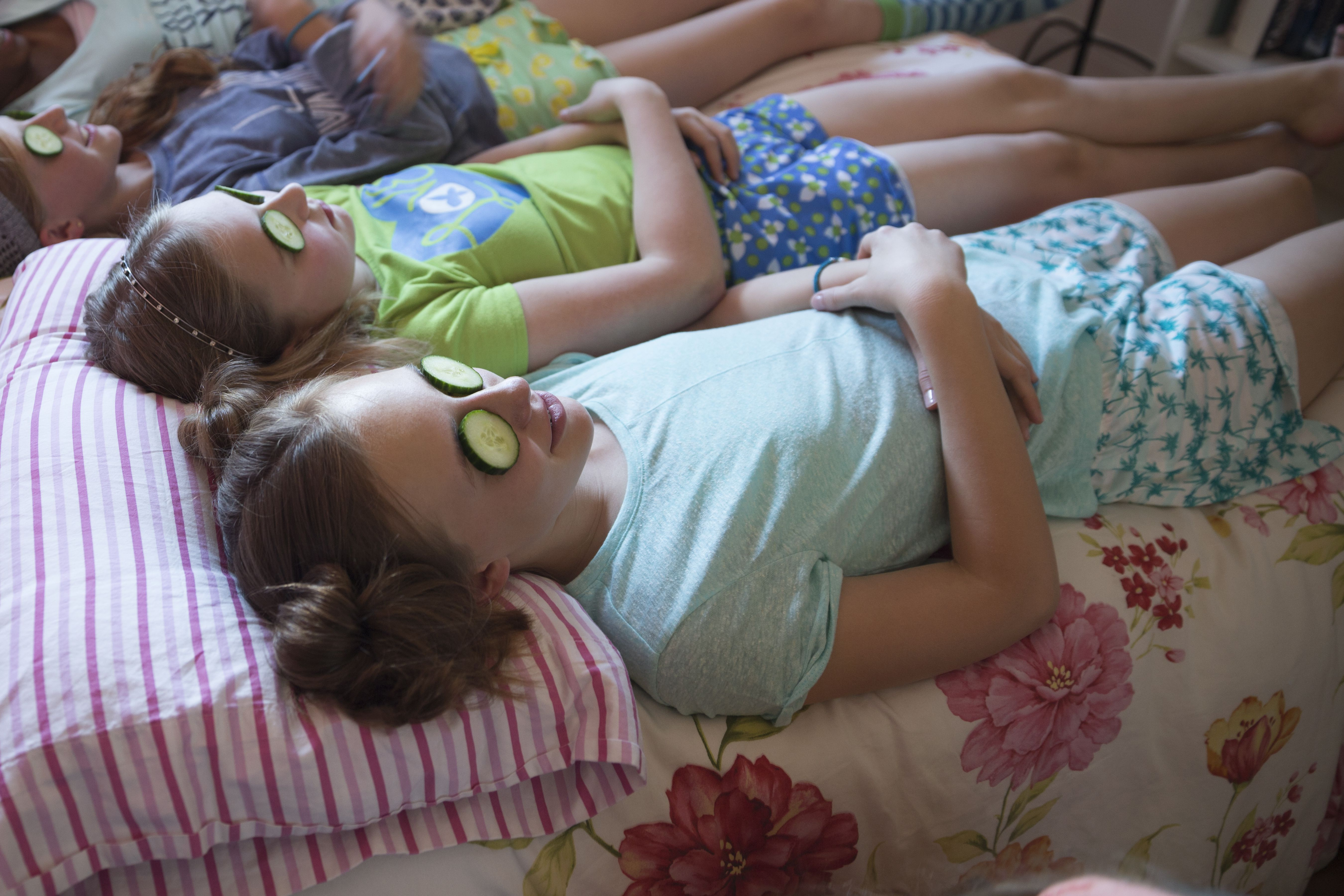 Girls relaxing with cucumbers on eyes at slumber party