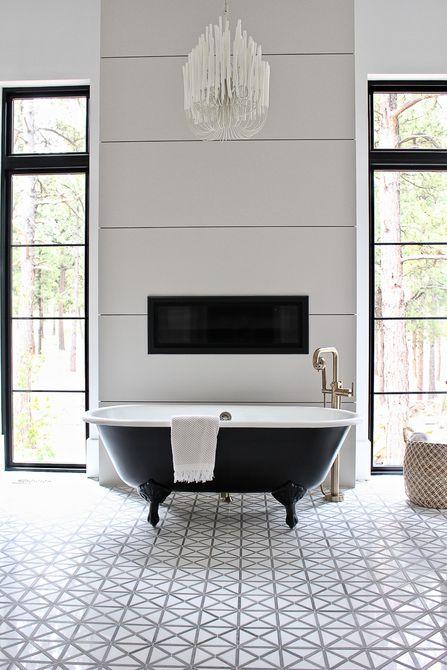 Baño con una bañera grande con patas negras